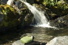Frasco en una piedra delante de una corriente de la montaña Foto de archivo