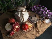 Frasco, maçãs, romã, copo do coffe com livros e laranja na ainda-vida conceptual da cortina da lona Fotografia de Stock Royalty Free
