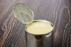 Frasco metálico com leite condensado do doce na tabela escura fotografia de stock royalty free
