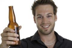 Frasco ocasional da terra arrendada do homem novo da cerveja, sorrindo Imagem de Stock Royalty Free