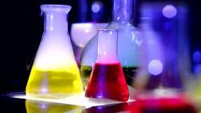 Frasco químico de ebullición con los líquidos multicolores almacen de metraje de vídeo