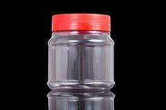 Frasco translúcido do PVC do plástico com a tampa vermelha isolada no preto imagens de stock royalty free