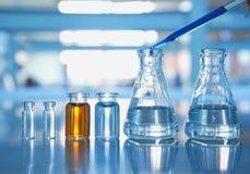 Frasco y frasco con la naranja y solución azul del descenso en laboratorio de ciencia Foto de archivo