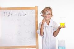 Frasco y lupa del químico de la muchacha en la pizarra Fotos de archivo libres de regalías