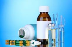 Frascos, ampolas e comprimidos médicos no azul Foto de Stock Royalty Free