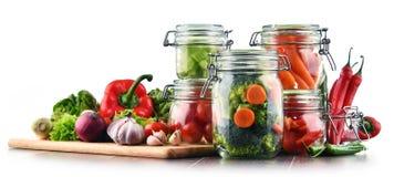 Frascos com alimento posto de conserva e os vegetais crus isolados no branco Fotografia de Stock