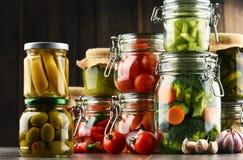 Frascos com alimento posto de conserva e os vegetais crus orgânicos Imagens de Stock