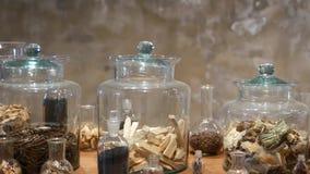 Frascos com as ervas secadas na loja do farmac?utico Frascos e garrafas de vidro com as ervas secadas sortidos da medicina coloca filme