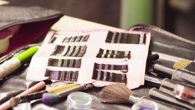 Frascos com as escovas brilhantes do pó e da composição filme