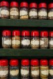 Frascos das ervas e das especiarias na cremalheira de madeira no fundo branco, projeto do vintage imagens de stock royalty free