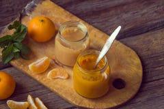 Frascos de vidro com comida para bebê natural com a tangerina no t de madeira Imagens de Stock Royalty Free