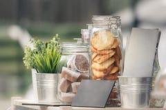 Frascos de vidro com cookies e queques, plântulas verdes em uns baldes decorativos do metal foto de stock