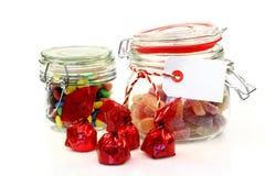 Frascos de vidro com doces e os bombons coloridos Foto de Stock