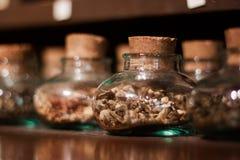 Frascos de vidro com ervas, especiarias, e chá Fotografia de Stock Royalty Free