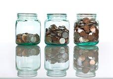 Frascos de vidro com moedas - conceito das economias Foto de Stock