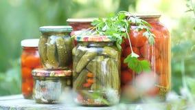 Frascos de vidro com vegetais salgados Colheita dos tomates e dos pepinos Tomates, pepinos, salgados para o inverno, a video estoque