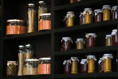 Frascos de vidro da cozinha bonita para armazenar produtos maiorias em uma prateleira escura com cereais, massa, especiarias e fe fotos de stock