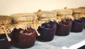 Frascos de vidro dos doces variados cobertos com o pano de saco e amarrados com corda imagem de stock