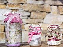 Frascos decorados com rosas e laço em um fundo de pedra Decoração Home Foto de Stock Royalty Free