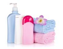 Frascos do champô e do gel com toalhas e flor foto de stock