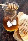 Frascos do favo de mel da abelha do mel e do pólen da abelha na tabela de madeira com favo de mel da cera Fotografia de Stock Royalty Free