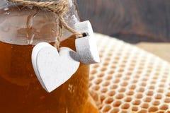 Frascos do favo de mel da abelha do mel e do pólen da abelha na tabela de madeira com favo de mel da cera Imagens de Stock Royalty Free