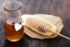 Frascos do favo de mel da abelha do mel e do pólen da abelha na tabela de madeira com favo de mel da cera Fotografia de Stock