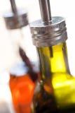 Frascos do petróleo verde-oliva e do petróleo do pimentão no restaurante Fotos de Stock