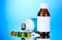 Frascos e comprimidos médicos no azul Fotografia de Stock