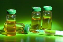Frascos médicos estéril con la solución, las ampollas, y la jeringuilla de la medicación en un fondo verde Imagen de archivo libre de regalías