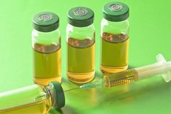 Frascos médicos estéril con la solución, las ampollas, y la jeringuilla de la medicación en un fondo verde claro Foto de archivo libre de regalías