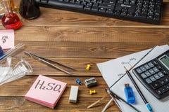 Frascos químicos, pinzas, teclado, cuadernos en una tabla de madera con copyspase Fotografía de archivo