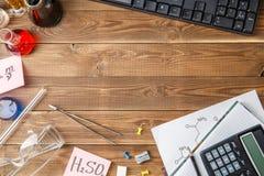 Frascos químicos, pinzas, teclado, cuadernos en una tabla de madera con el copyspace Fotografía de archivo libre de regalías