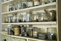 Frascos velhos do vário vintage com parafusos, porcas e parafusos do metal no armário de madeira na oficina Foto de Stock Royalty Free