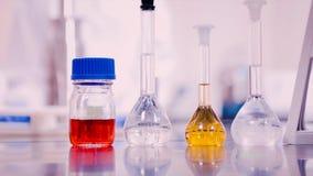 Frascos y cubiletes del laboratorio con los líquidos de diversos colores en la tabla del laboratorio Imágenes de archivo libres de regalías