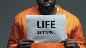 Frase de la cadena perpetua en la cartulina en manos del preso peligroso afroamericano almacen de video