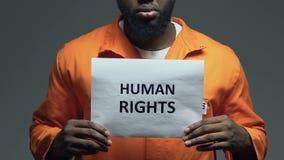 Frase de los derechos humanos en la cartulina en las manos del preso afroamericano, asalto metrajes