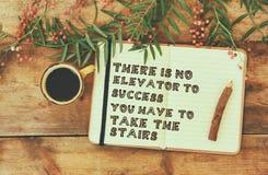 Frase del éxito y de la inspiración abra el cuaderno con el texto al lado de la taza de café sobre la tabla de madera imagen filt Imágenes de archivo libres de regalías