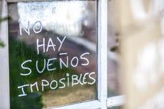 Frase dell'ottimista scritta sopra i vecchi vetri di finestre nello Spagnolo Fotografia Stock Libera da Diritti