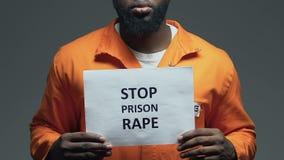 Frase della violenza della prigione di arresto su cartone in mani del prigioniero afroamericano video d archivio