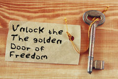 A frase - destrave a porta dourada da liberdade escrita na nota unida à chave Fotos de Stock Royalty Free