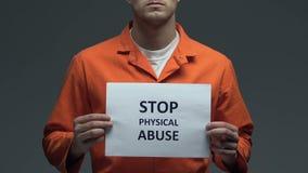 Frase di abuso fisico di arresto su cartone in mani del prigioniero caucasico, violenza archivi video