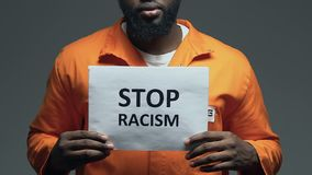 Frase di razzismo di arresto su cartone in mani del prigioniero nero, distinzione stock footage