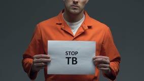 Frase di TB di arresto su cartone in mani del prigioniero caucasico, bisogno di sanità stock footage