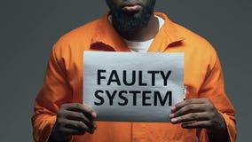 Frase difettosa del sistema su cartone in mani del prigioniero afroamericano, disordine stock footage