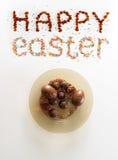 Frase felice di Pasqua fatta dall'uva passa e dallo zucchero variopinto di cottura sopra fondo bianco con un piatto pieno delle u Immagine Stock Libera da Diritti