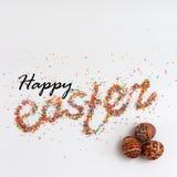 Frase felice di Pasqua fatta dallo zucchero variopinto di cottura e dalle uova disegnate a mano variopinte Fotografia Stock