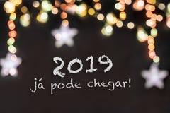 Frase portuguesa sobre Noche Vieja en un fondo negro con las luces borrosas imagen de archivo