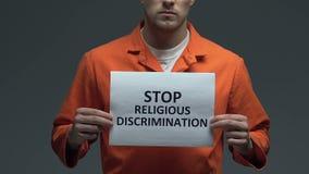 Frase religiosa da discriminação da parada no cartão nas mãos do prisioneiro caucasiano filme