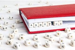 Frase sobre nosotros escritos en bloques de madera en cuaderno rojo en pizca Imagen de archivo libre de regalías